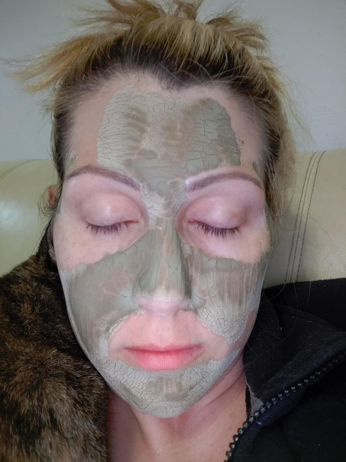 A reviewer wearing the clay mask on their face