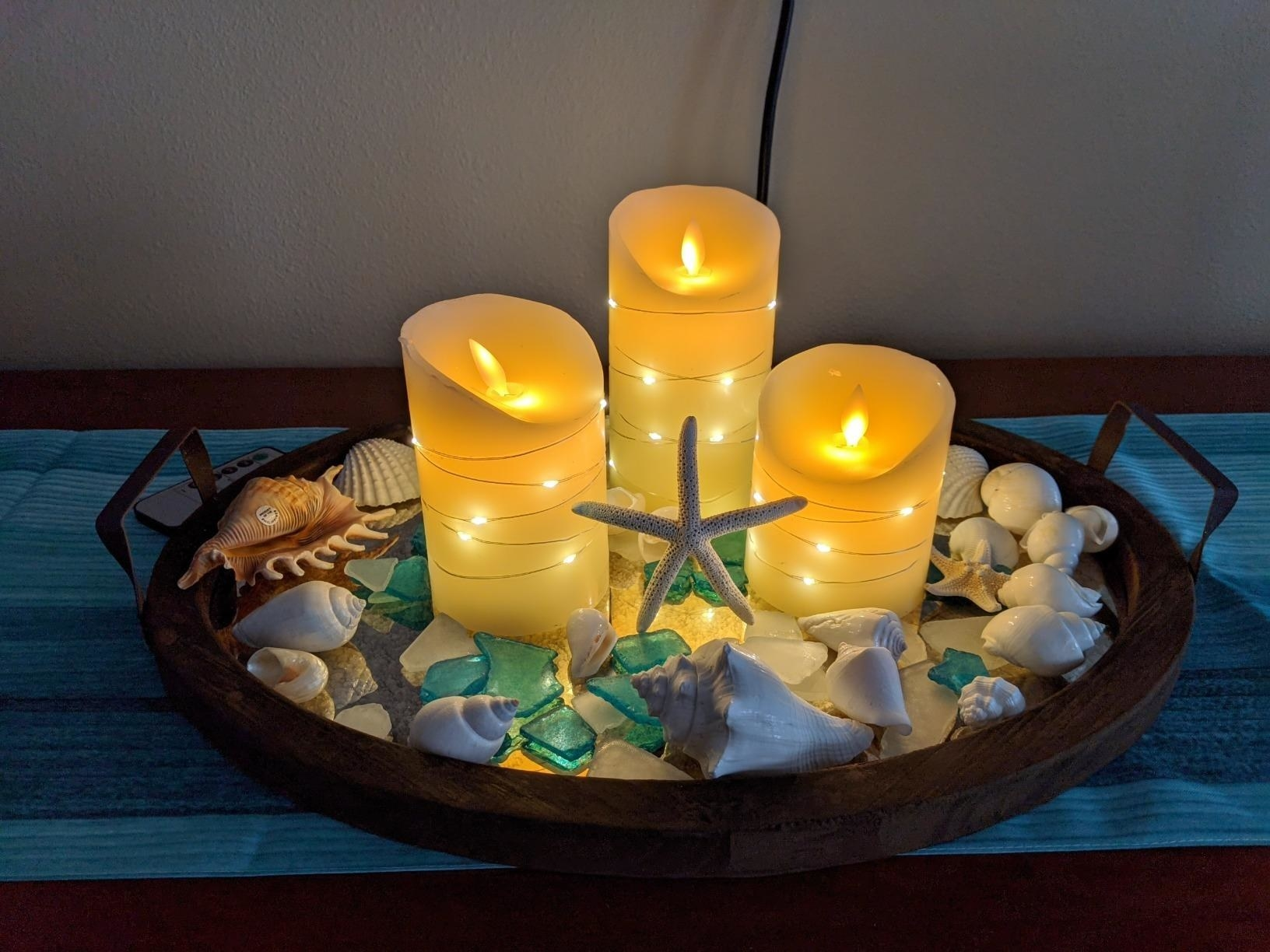 A reviewer's three candles in different heights on a tray