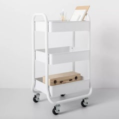 A white 3 tier cart on wheels filled with craft supplies
