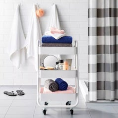 A white 3 tier cart on wheels filled with bathroom towels and accessories