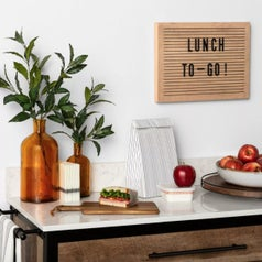 A countertop with vases, cutting board, and brown wooden lazy susan holding a bowl of apples