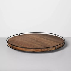 A brown wooden lazy susan with metal edges, side view