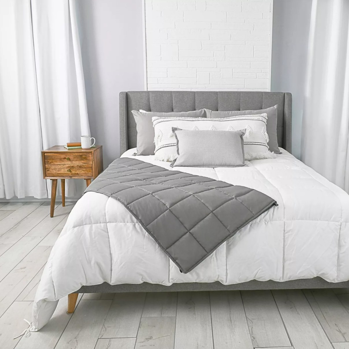 A gray weighted blanket lying across a white bed
