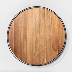 A brown wooden lazy susan with metal edges