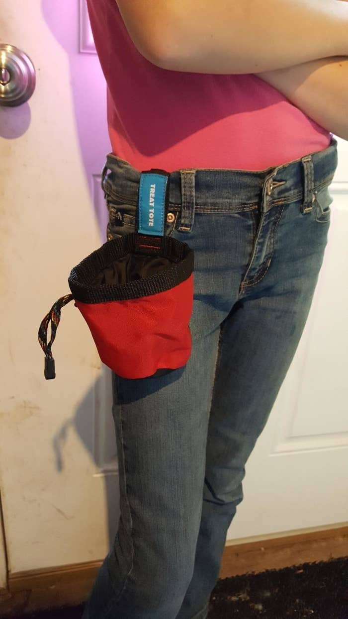Amazon customer stands with red and black treat tote clipped to their jeans