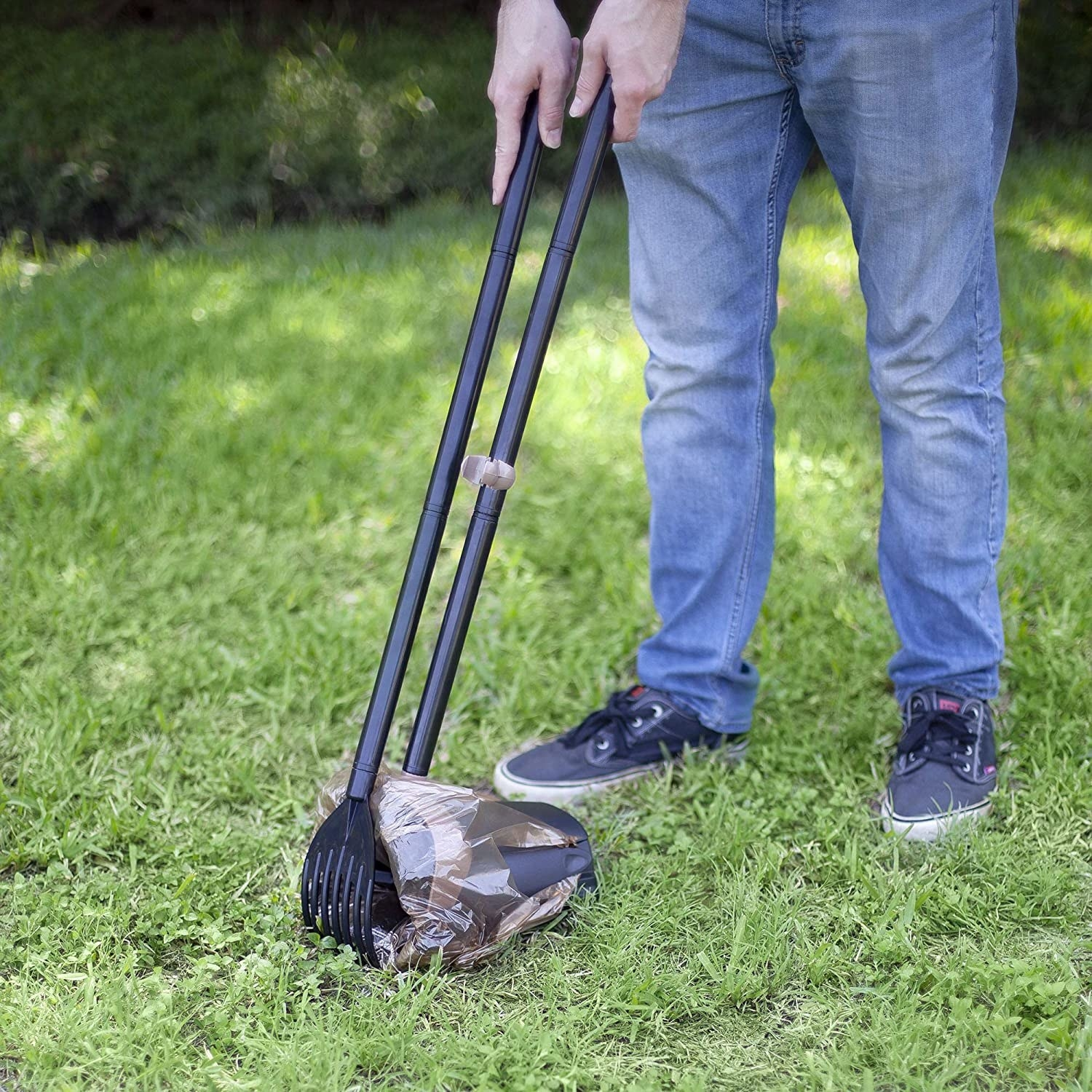 Black scooper and rake with a brown plastic bag covering