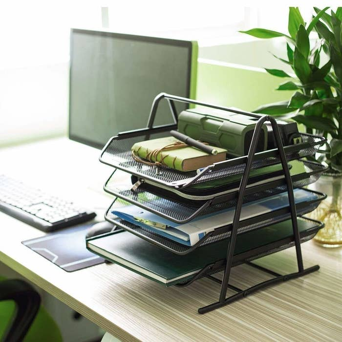 A four-tier mesh organiser pictured on a desk.