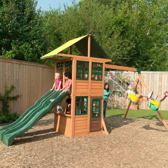 Brown swing set with green slides, roof, and window, and yellow swings