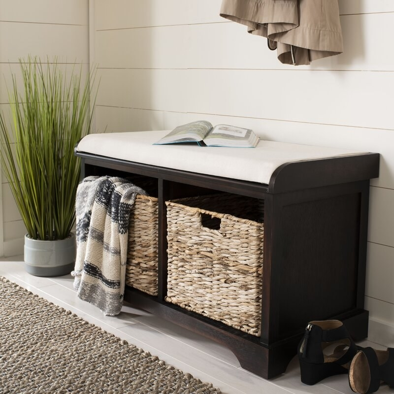 A storage bench with a cushion on top and storage baskets