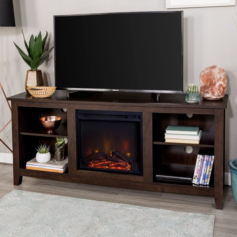 A brown wooden TV stand with storage shelves and electric fireplace with heater