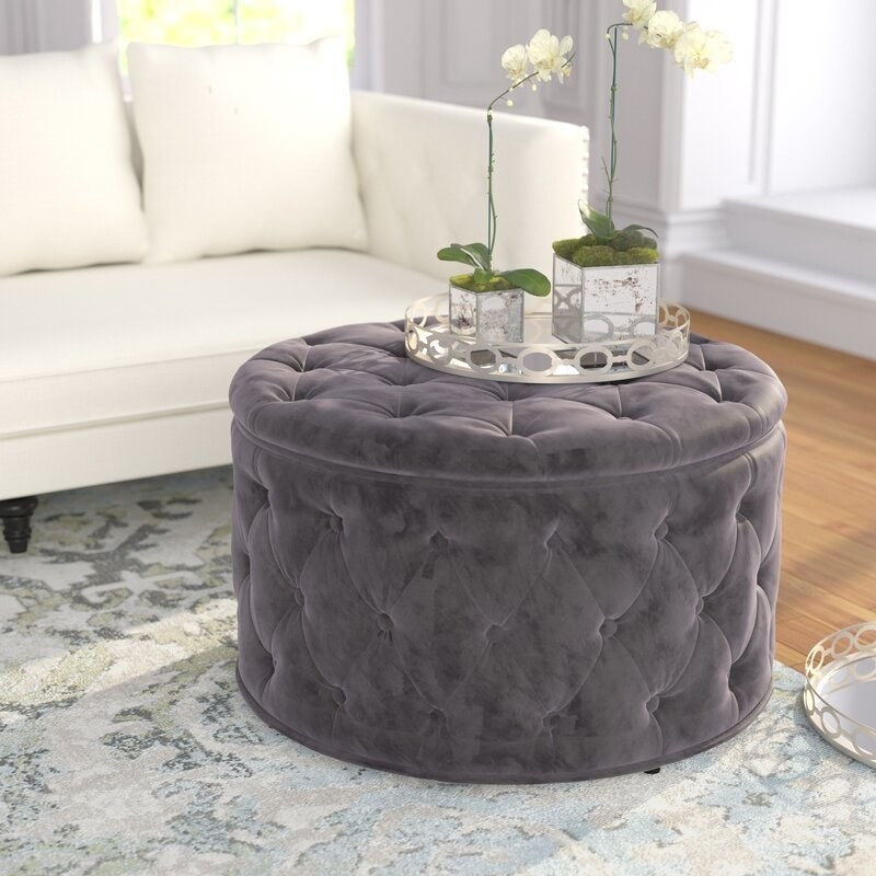 A round gray tufted ottoman