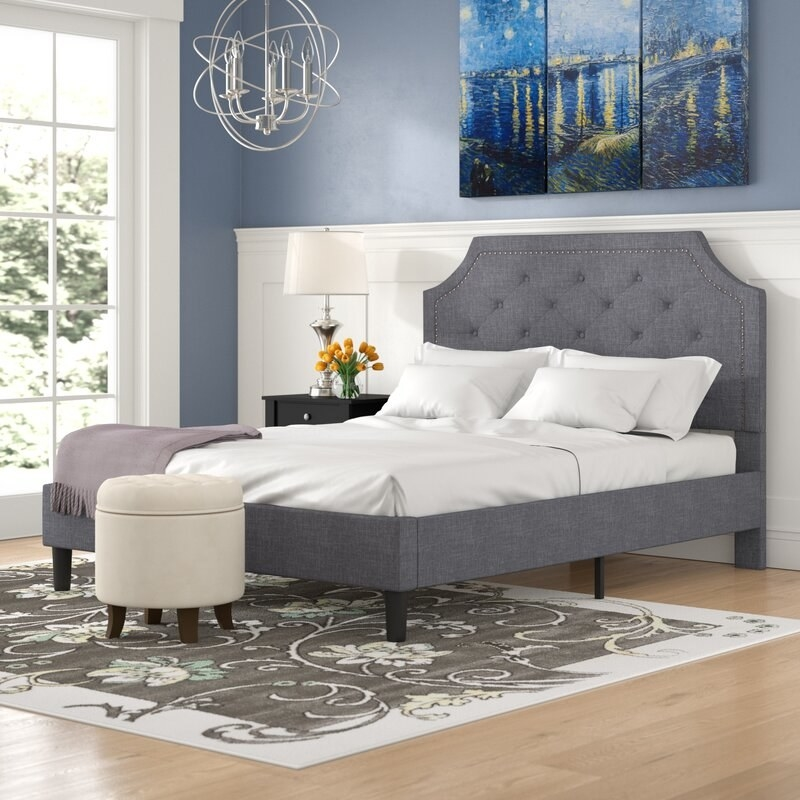 A gray upholstered bed frame with tufted headboard