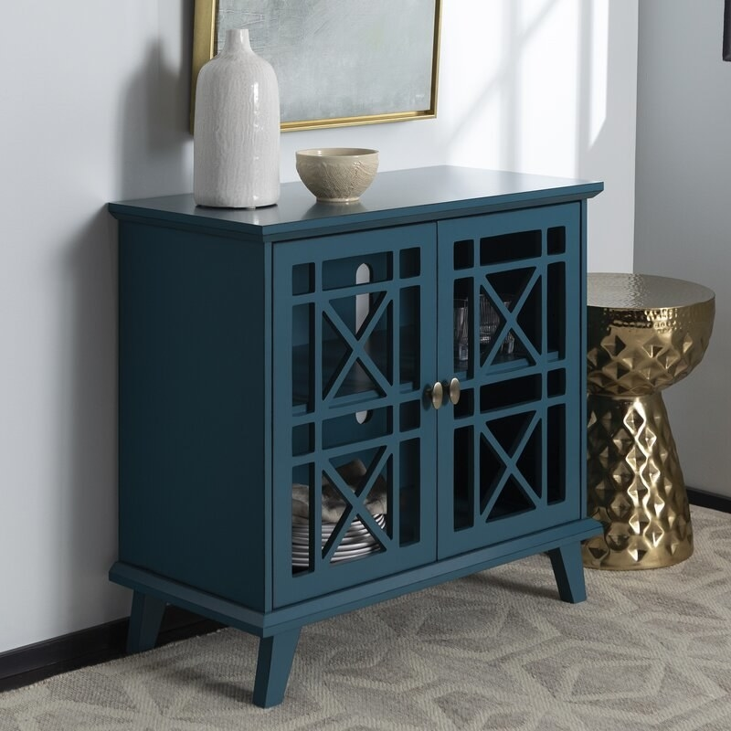 A blue accent cabinet with decorative doors