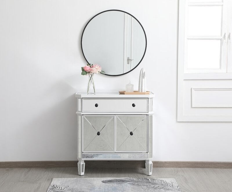 A mirrored storage cabinet with a drawer