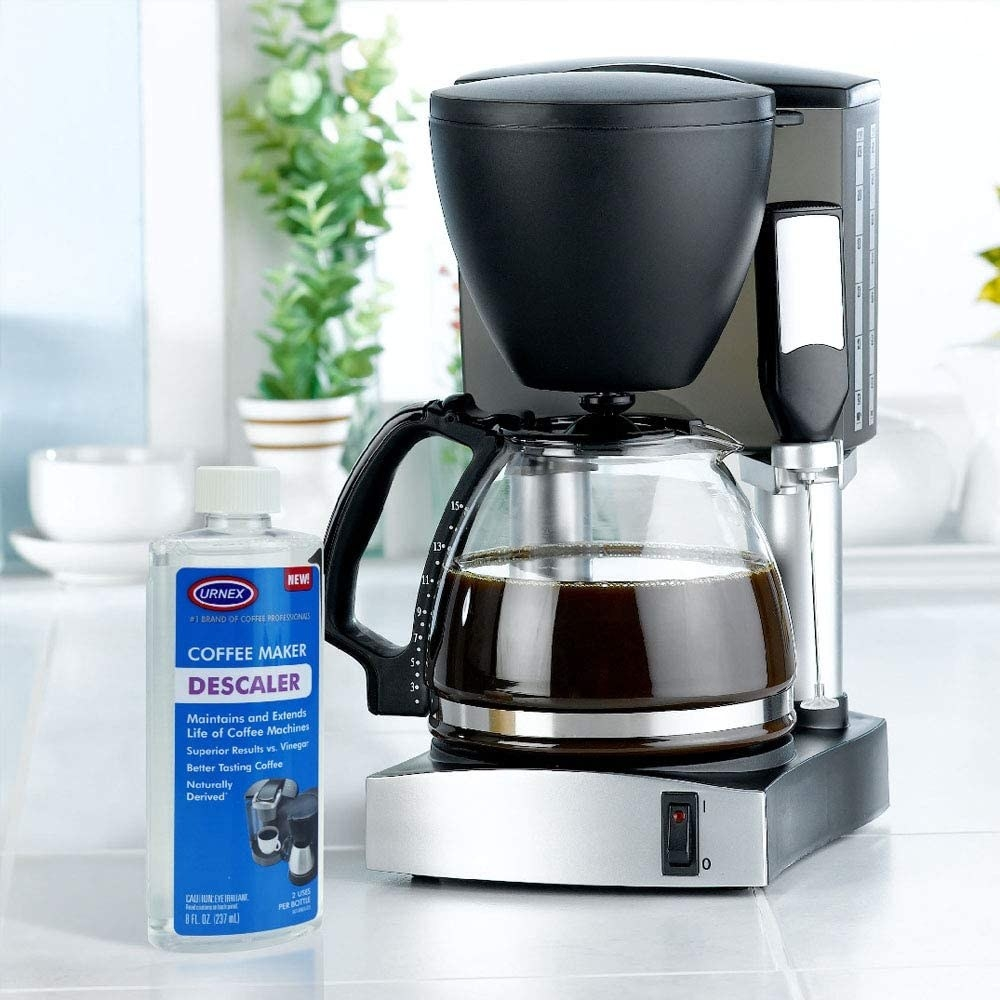 A bottle of descaling solution next to a coffee maker