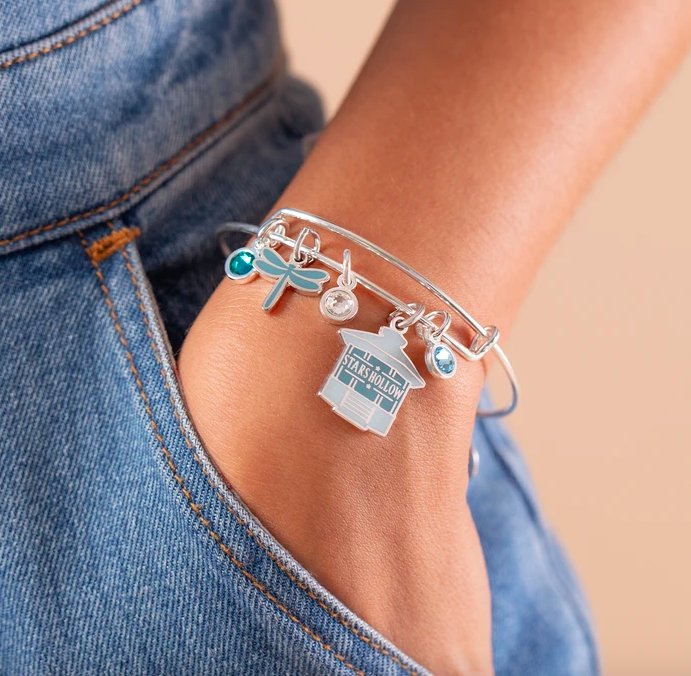 A model wears the gilmore girls stars hollow multi-charm bangle on their wrist