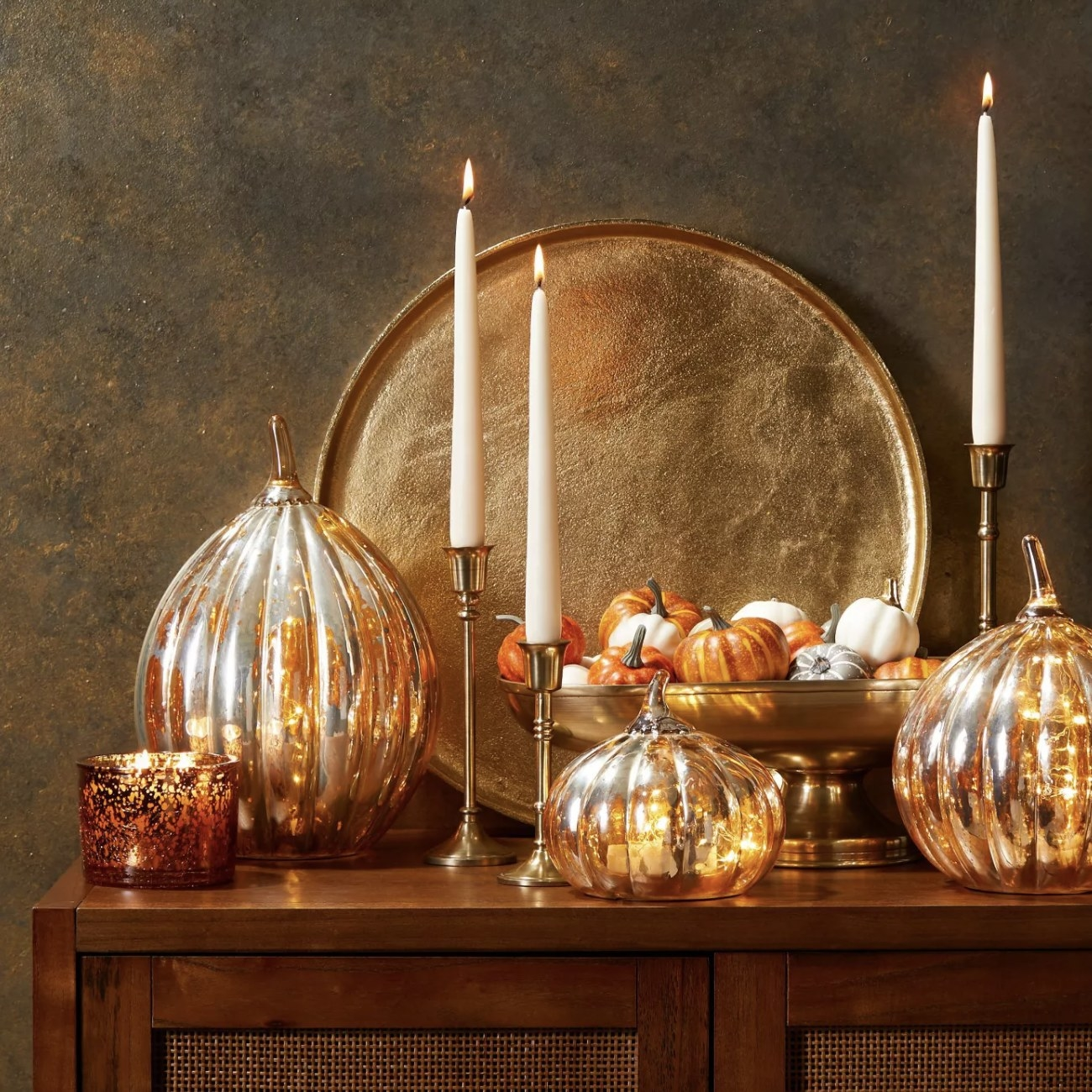 Three gold candle holders next to decor on a buffet