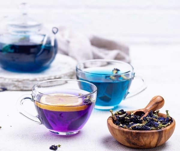 A cup of blue butterfly pea flower tea and cup with lemon that has turned the tea purple.