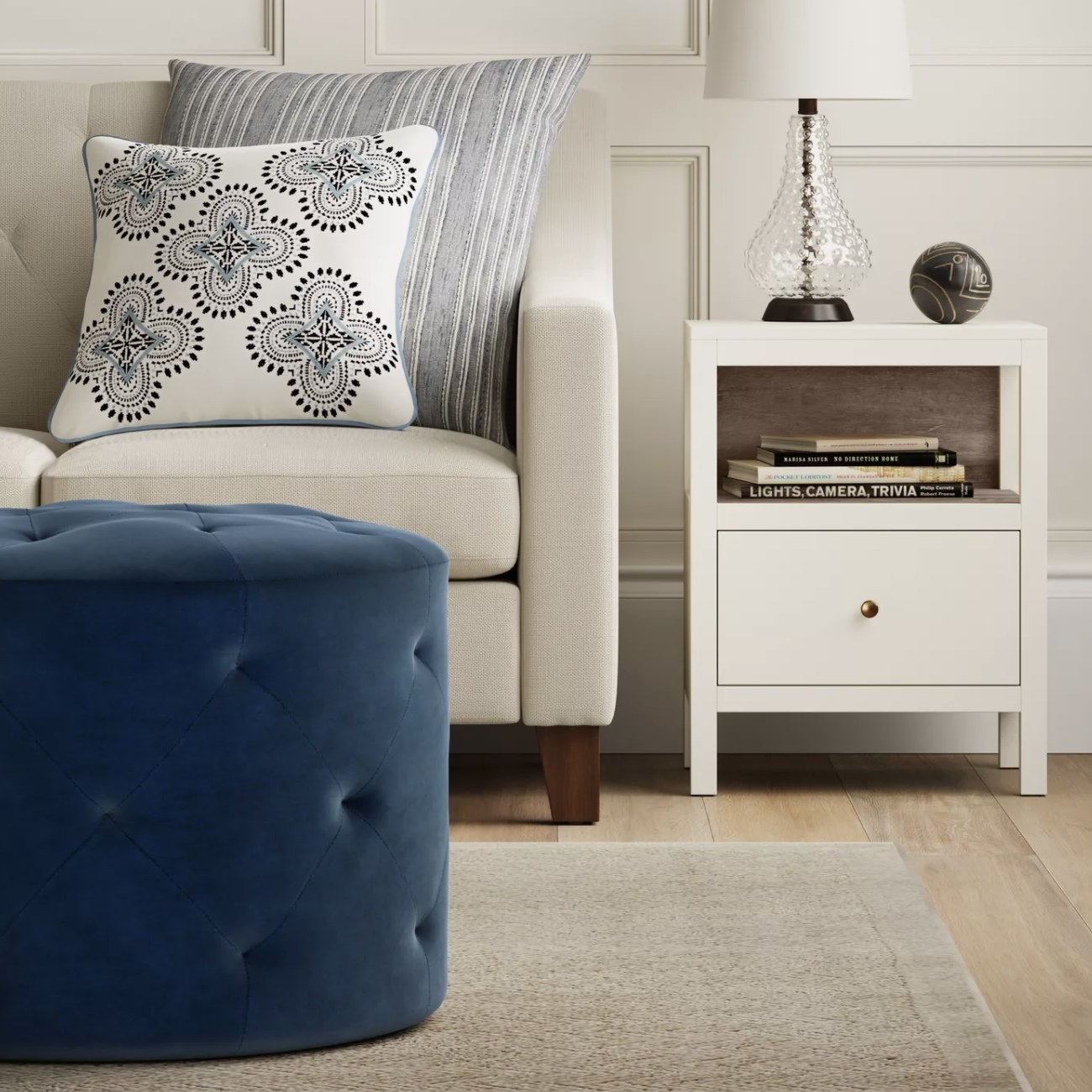 A dark blue tufted ottoman in a living space