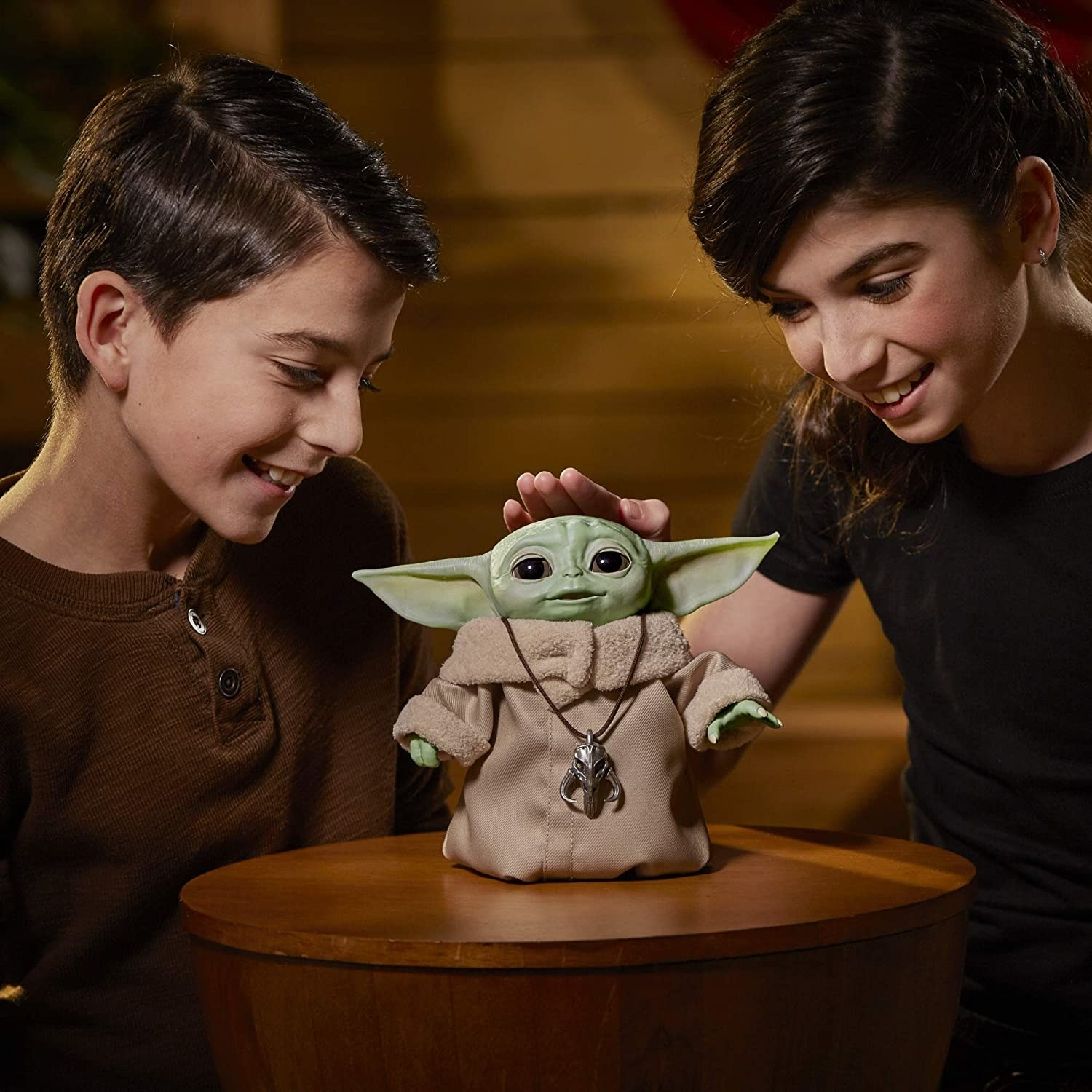 Two children playing with the interactive baby yoda