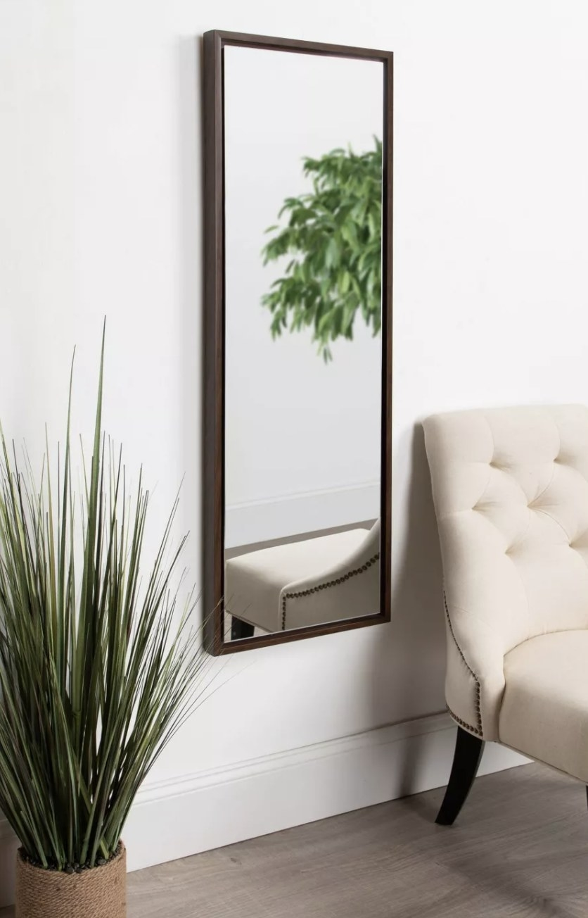 The full-length mirror mounted on a wall