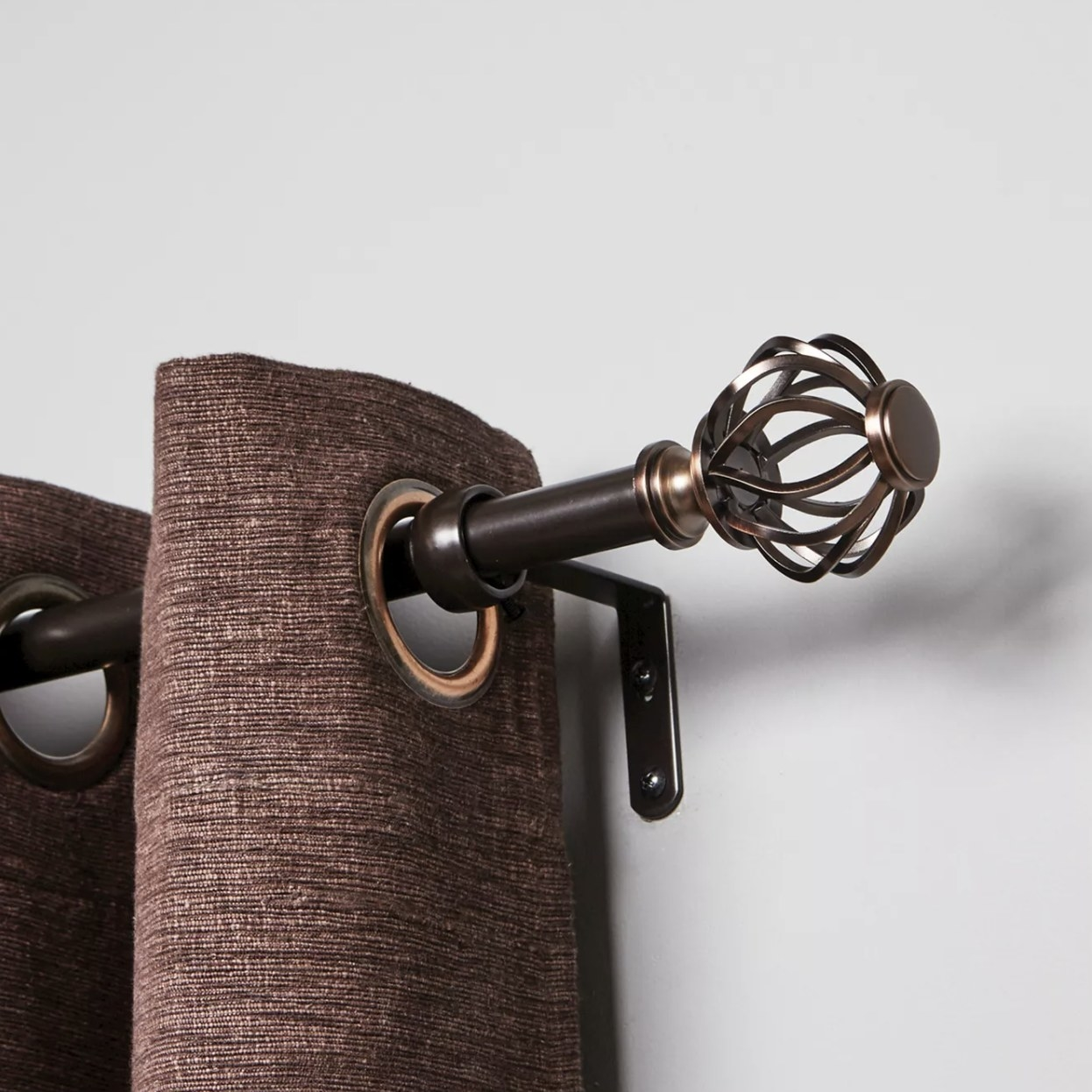 A bronze curtain rod with a brown curtain on it
