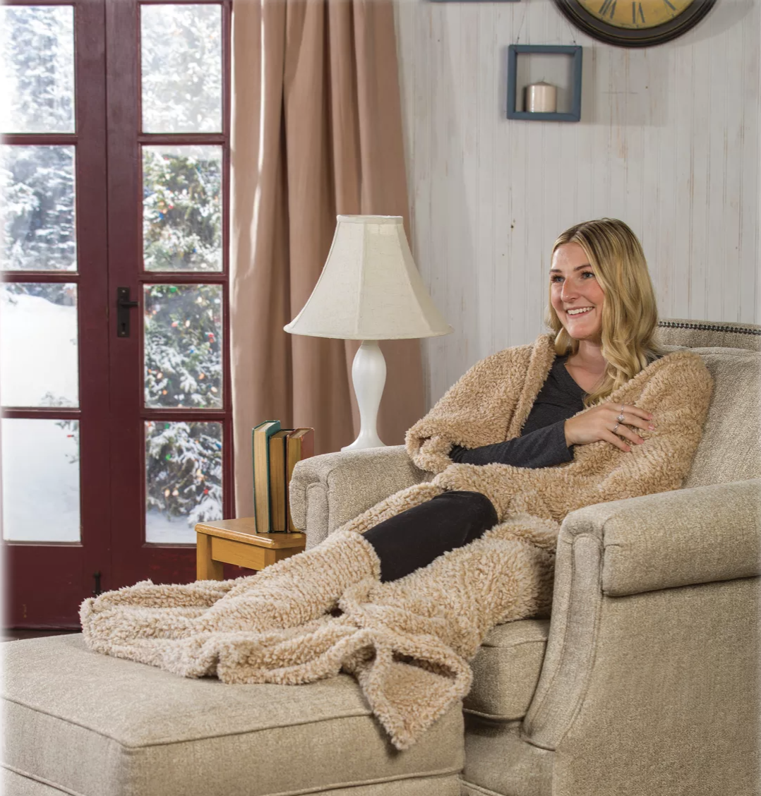 Model with the beige blanket wrapped around them and their feet in the deep pockets at the bottom