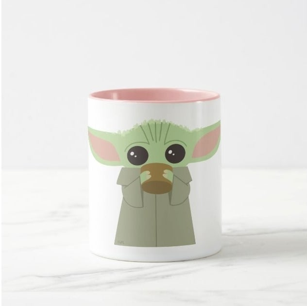 White mug with an illustration of Baby Yoda drinking out of a coffee cup on it