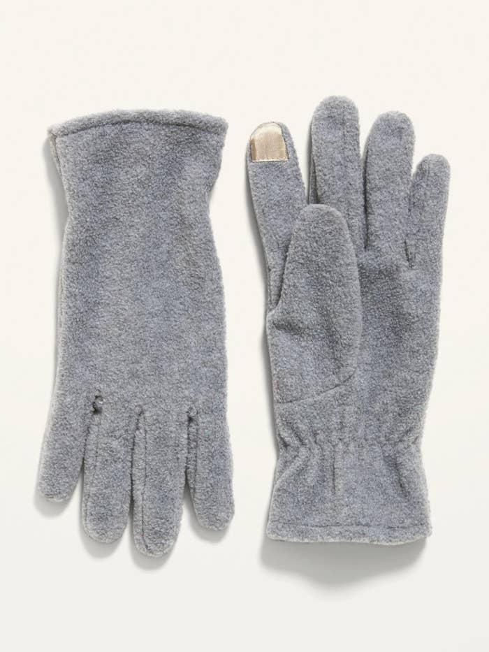A grey pair of fleece gloves with a smooth surface on the tip of one of the fingers for texting