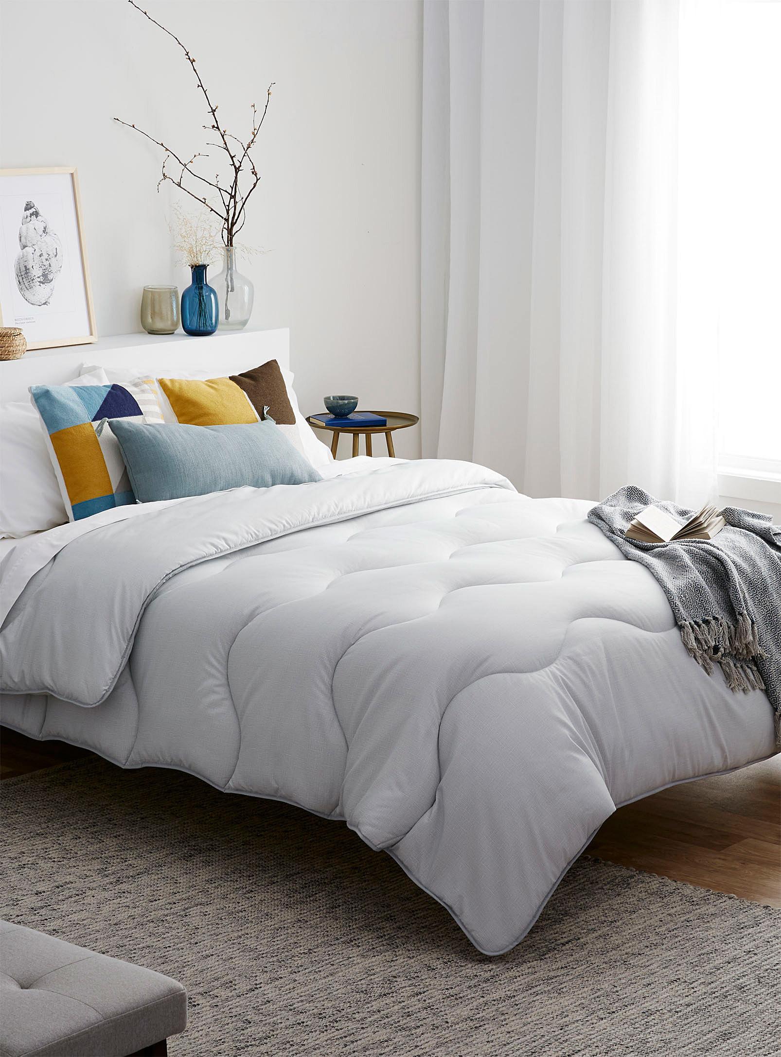 A lightweight duvet on a bed with pillows