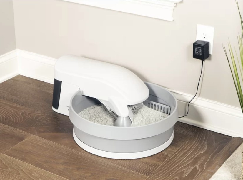 Gray round litter box with white conveyor apparatus, plugged into wall