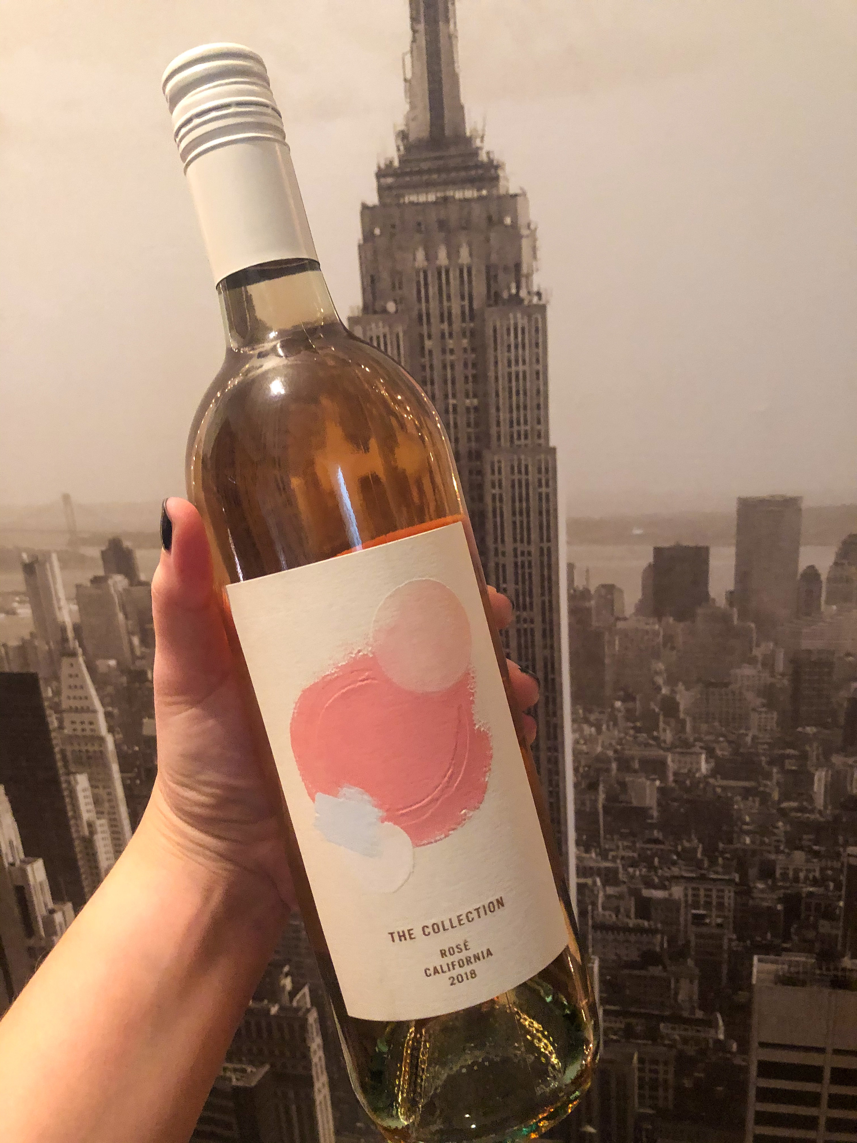 A hand holding a bottle of The Collection rosé in front of a portrait of NYC