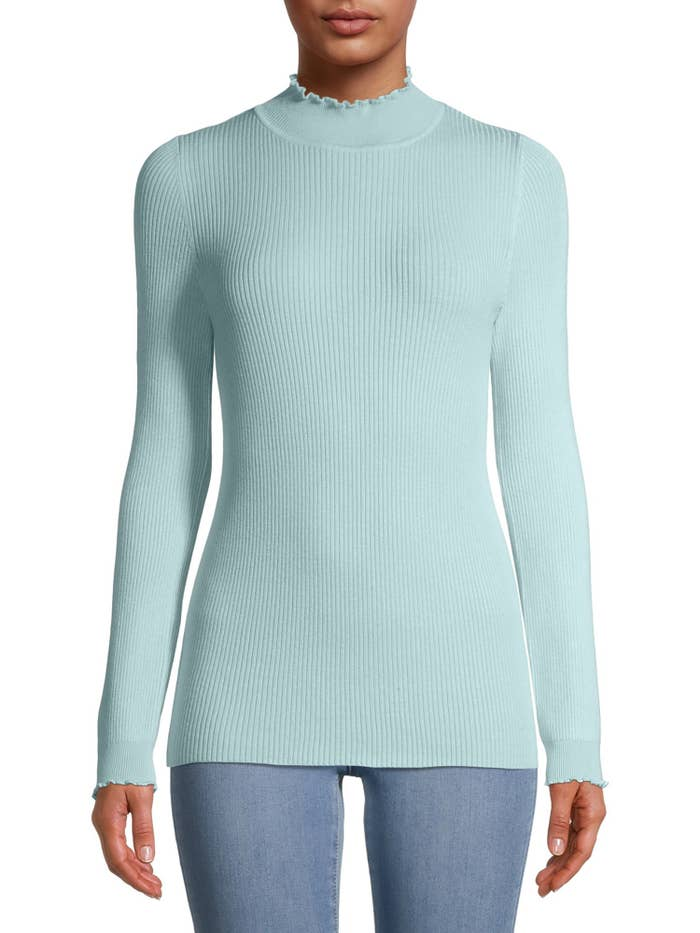 Model wearing light blue sweater with ruffled neckline