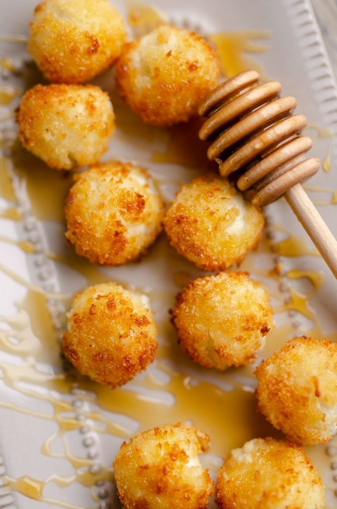 Several breaded goat cheese balls on a plate with a honey drizzle.