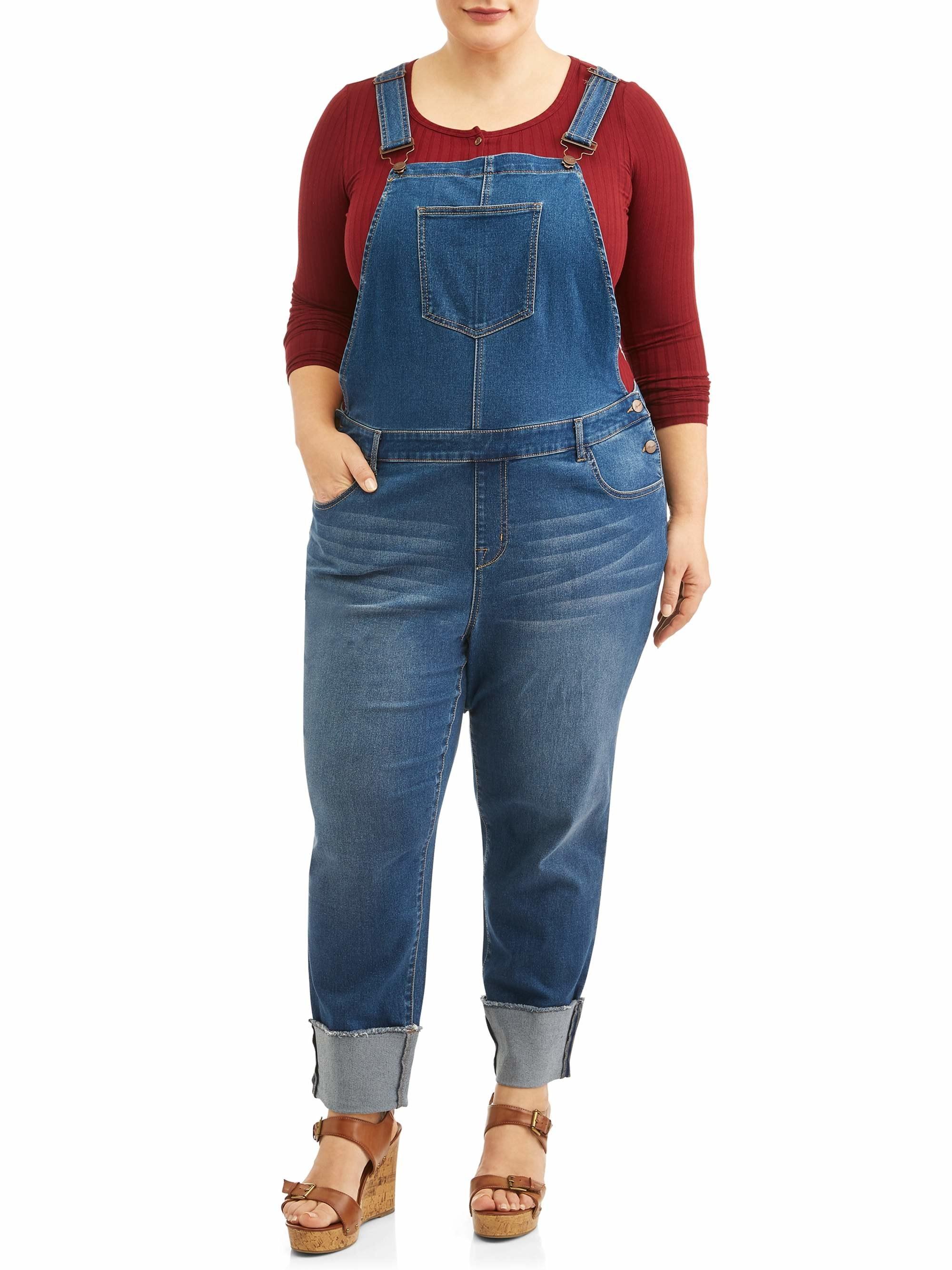 Model wearing medium wash denim overalls