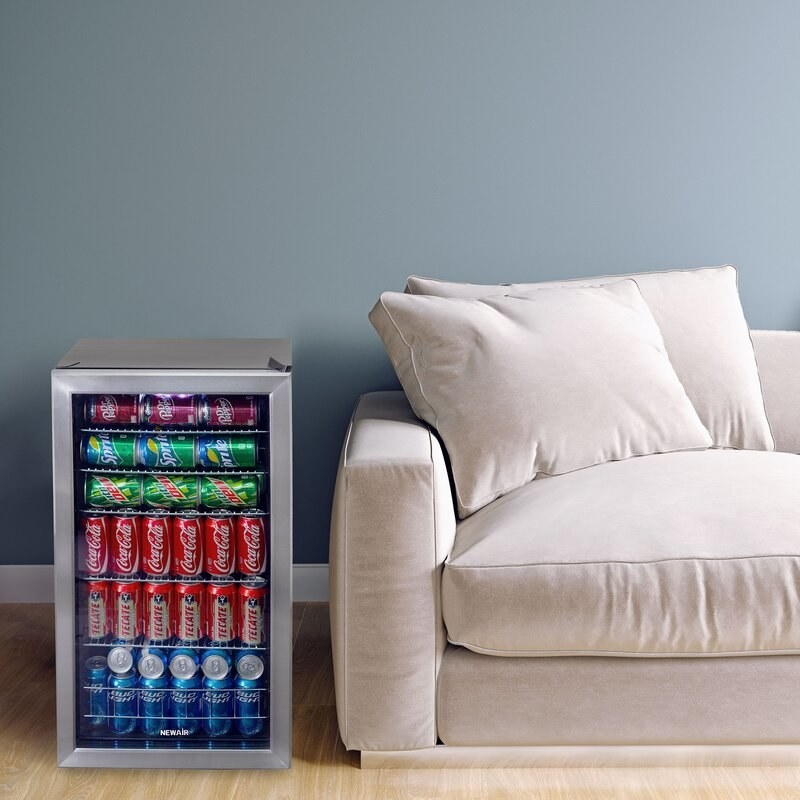 Gray drink fridge with silver and clear door beside a cream colored couch