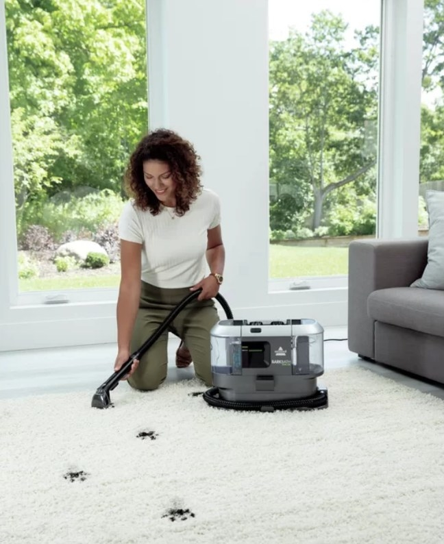 Model using Bissell carpet cleaner on white carpet with black paw prints