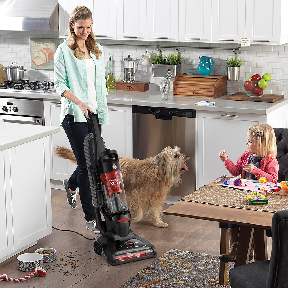 person using hoover upright vacuum to clean up a mess in a kitchen