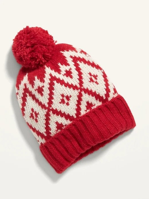 A red and white hat with a fuzzy ball at the top