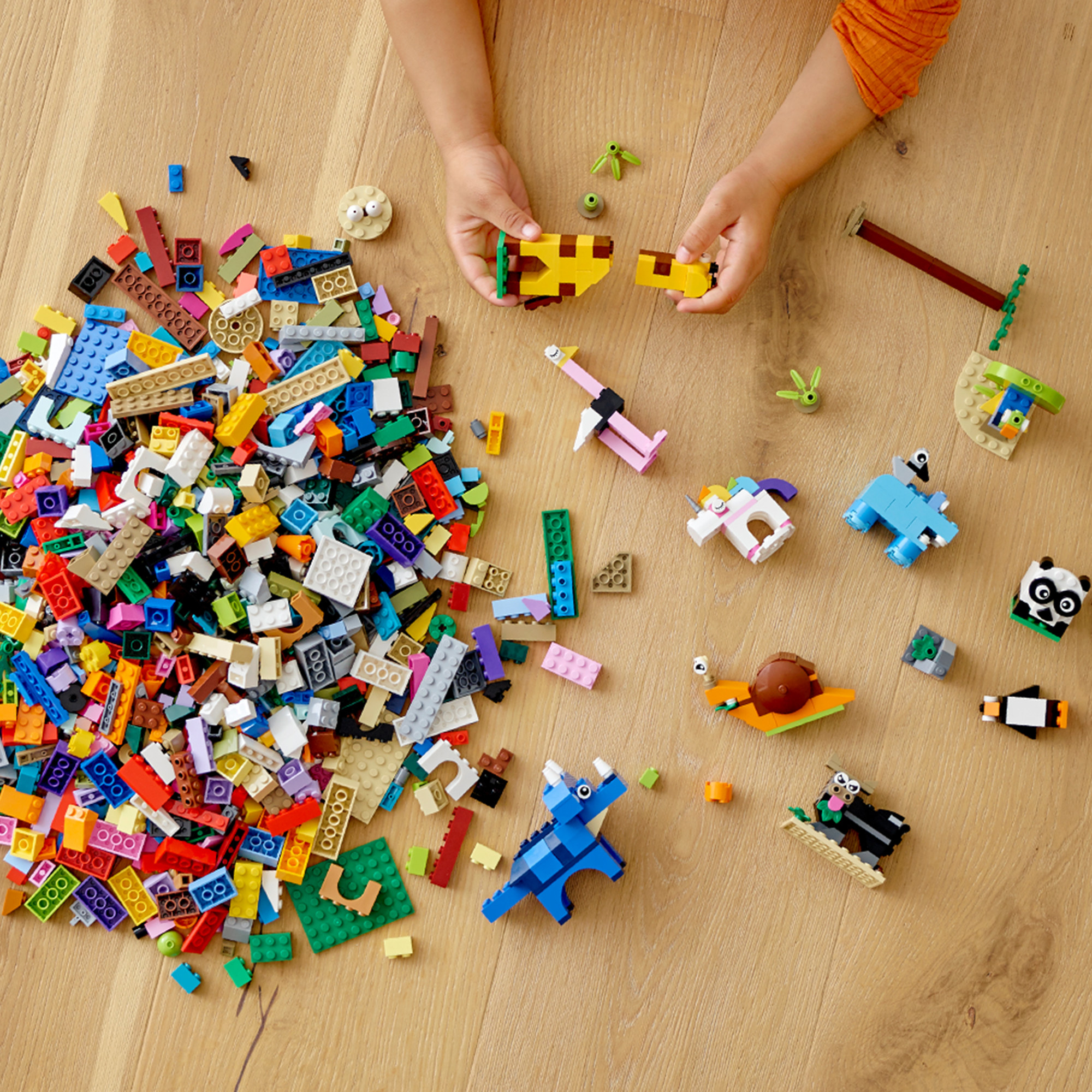 child playing with giraffe blocks with lots of colorful lego bricks lying around