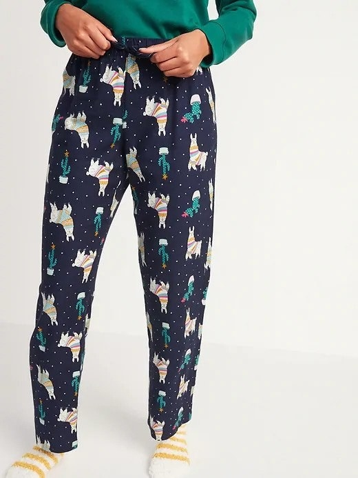 A woman wearing blue and green pajama pants with llamas printed on them