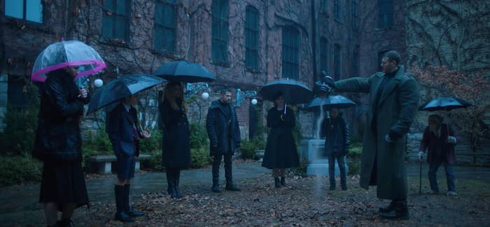 The Hargreeves stand outside in the rain as they pour Reginald's ashes on the ground