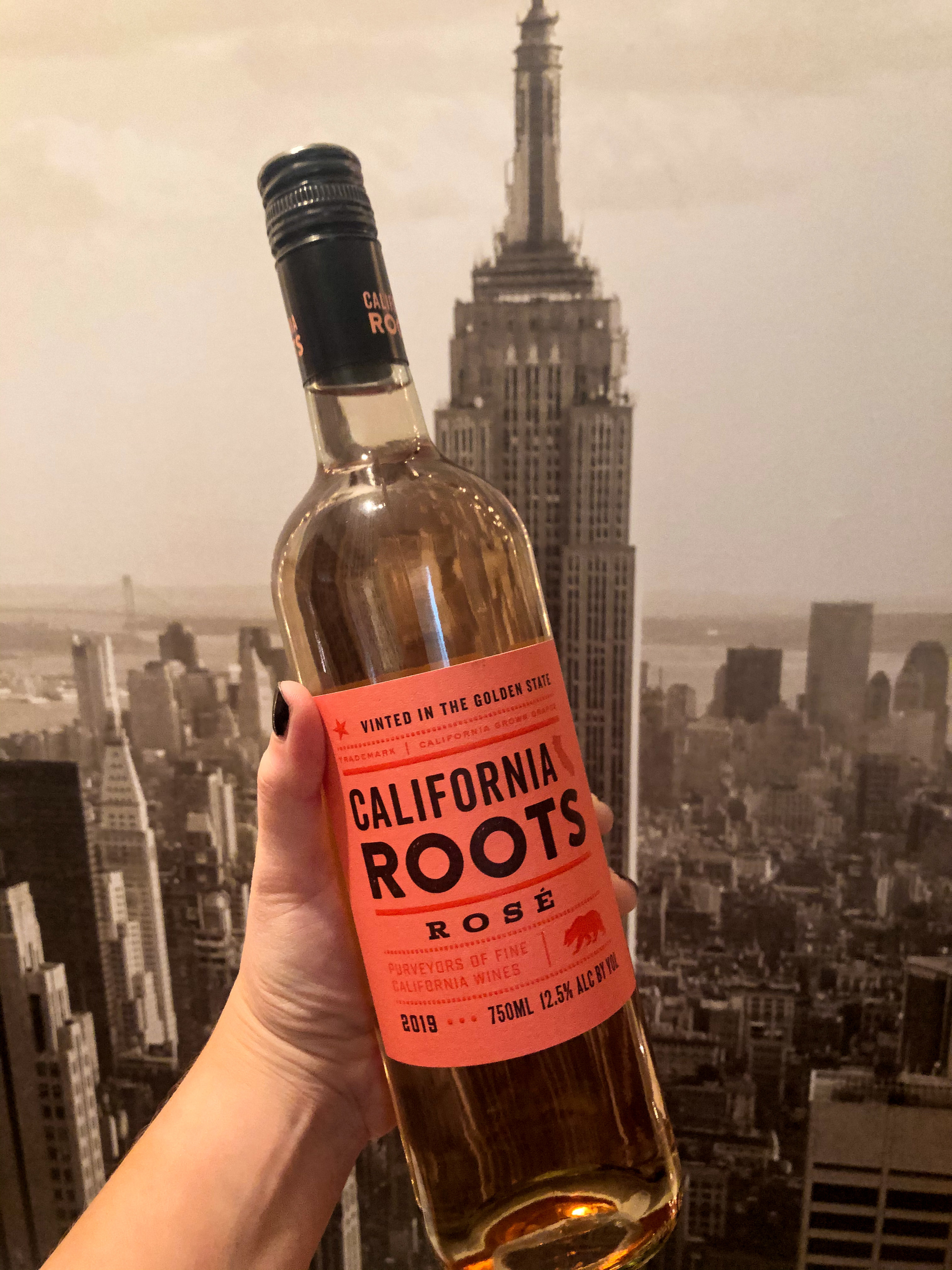 A hand holding a bottle of California Roots rosé in front of a portrait of NYC