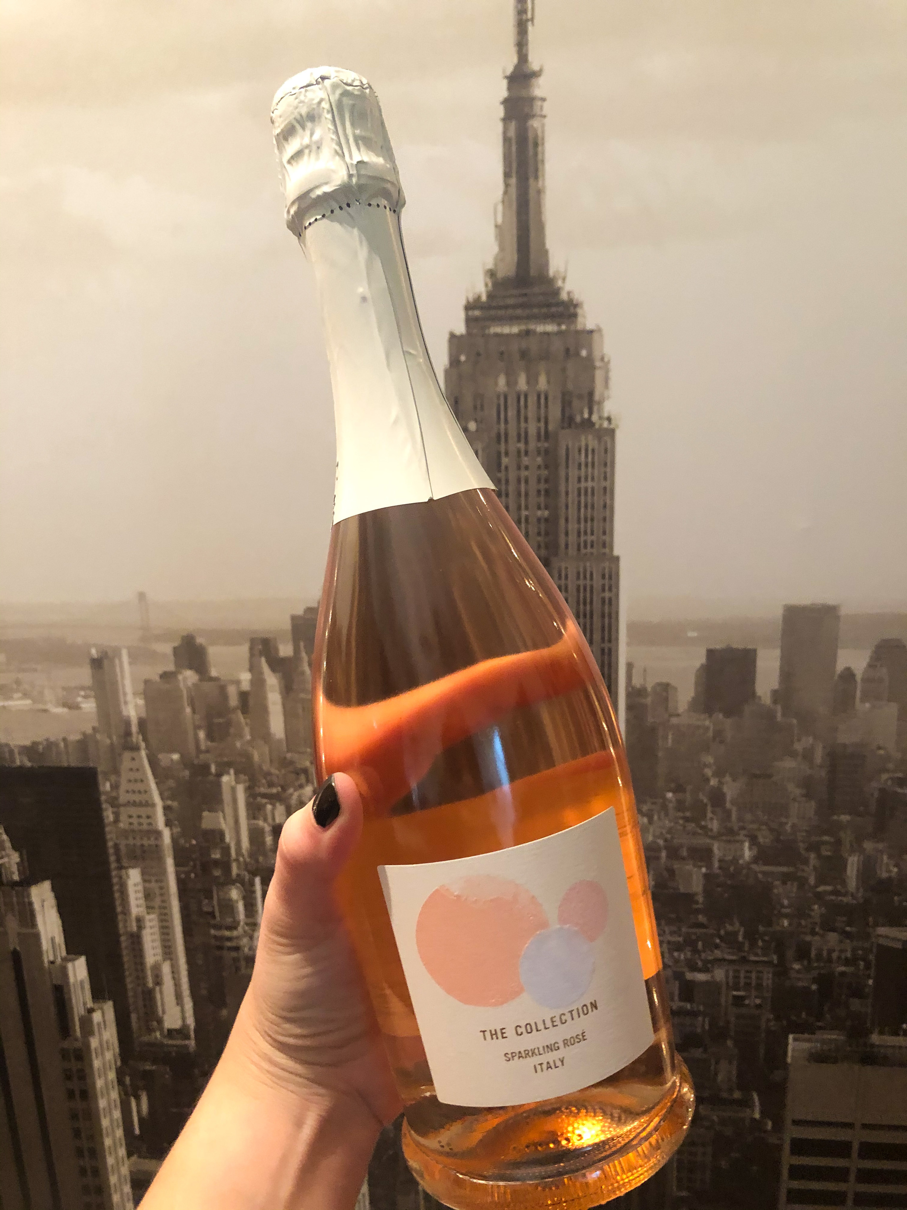 A hand holding a bottle of The Collection sparkling rosé in front of a portrait of NYC