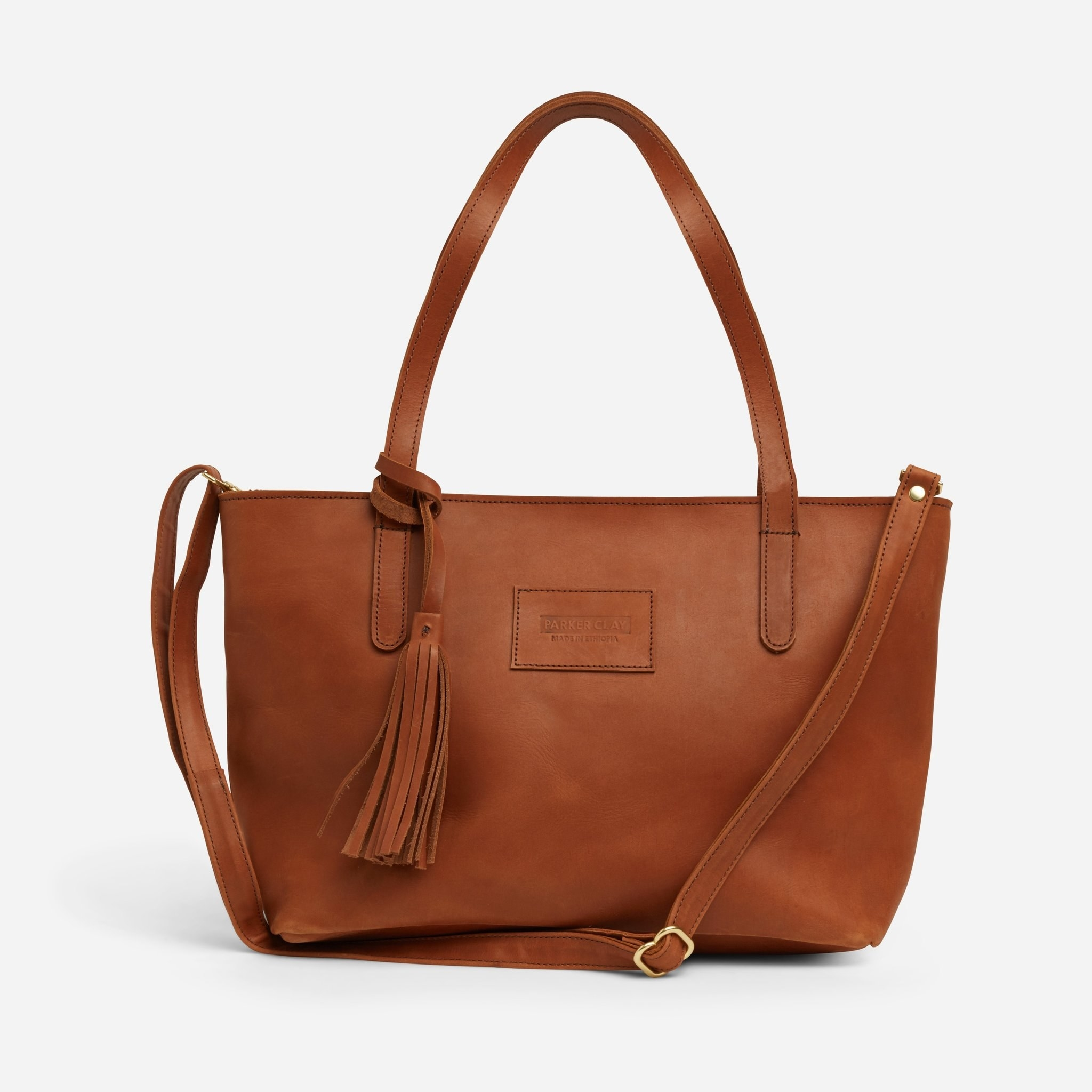 cognac brown tote bag with a crossbody strap and fringe accent