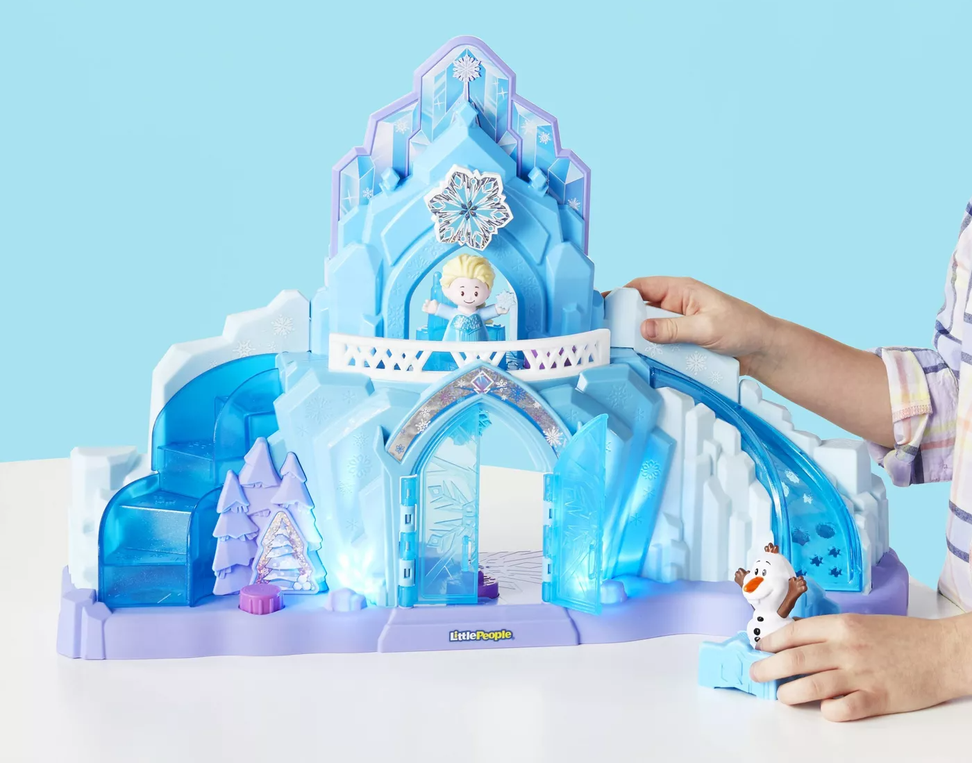 Child's hand playing with blue and purple ice castle toy and figures