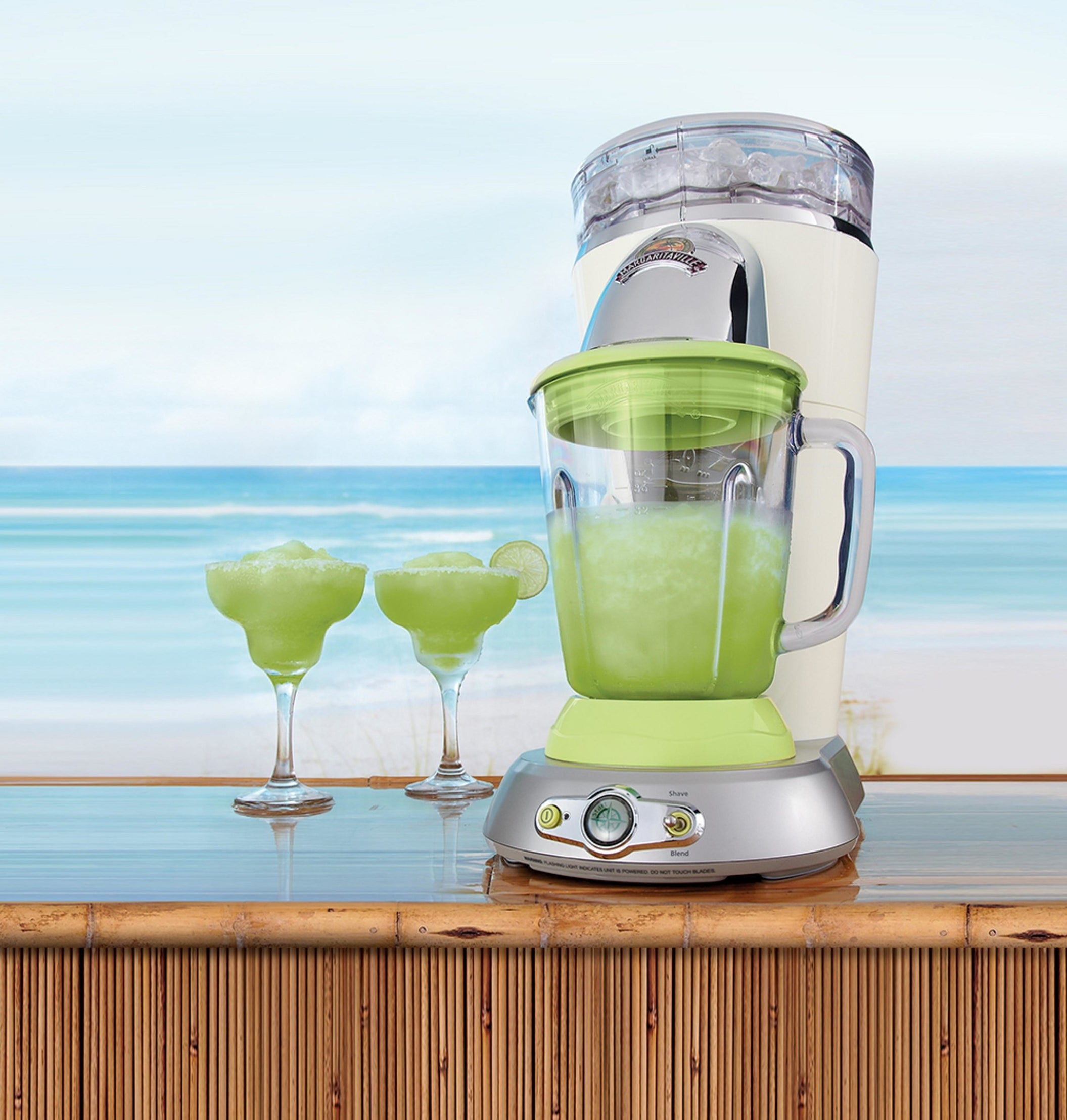 margaritaville frozen drink maker with a margarita in it and two margarita glasses on the bar