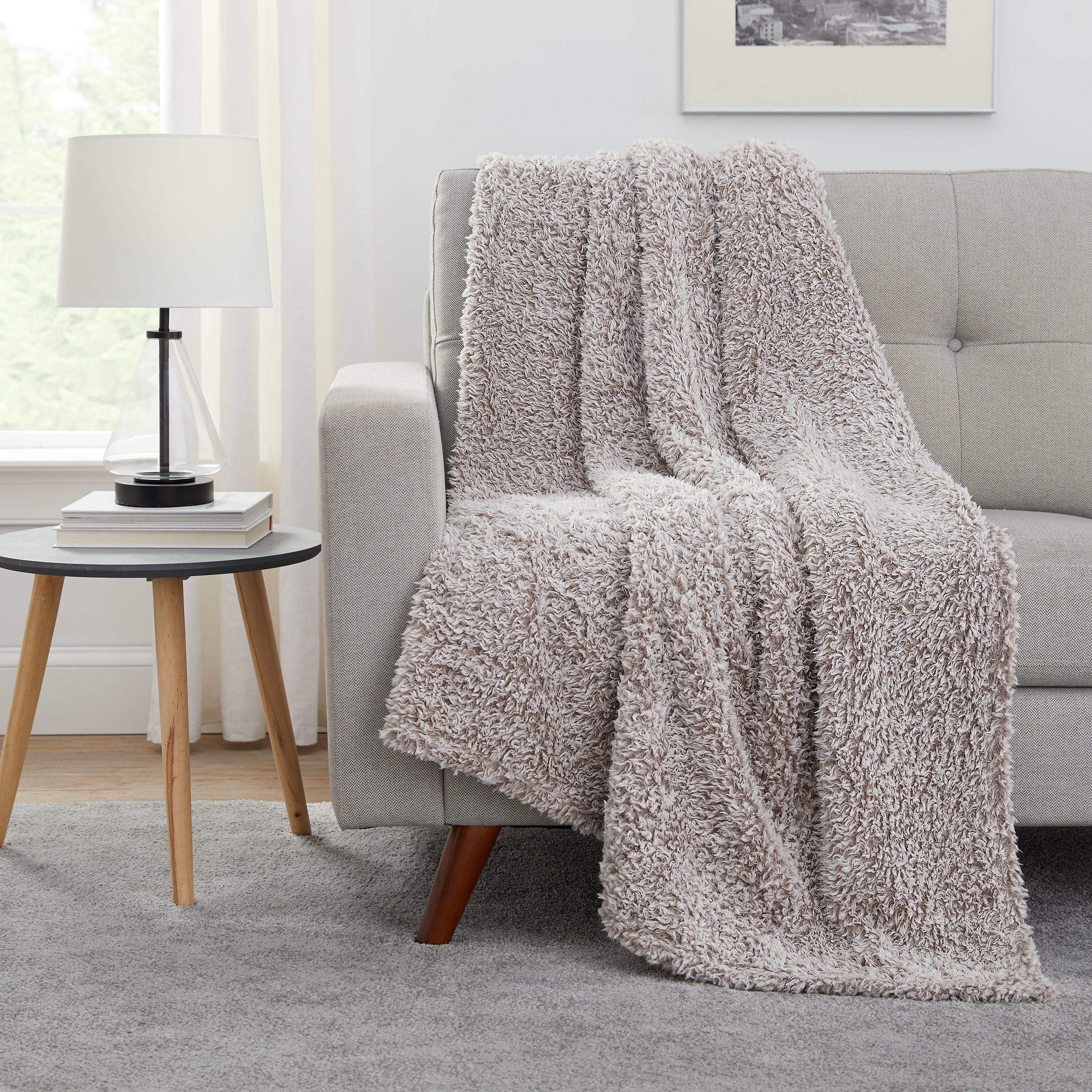 The sherpa throw in light brown draped over a couch