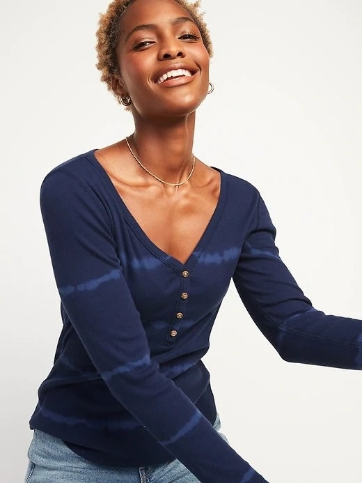 A woman wearing a blue v-neck long sleeve tee shirt with light brown buttons running up the middle of the top half