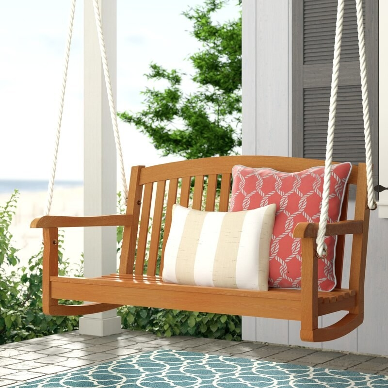 Brown porch swing with white ropes and displaying a white and tan striped pillow and red pillow with a white rope design